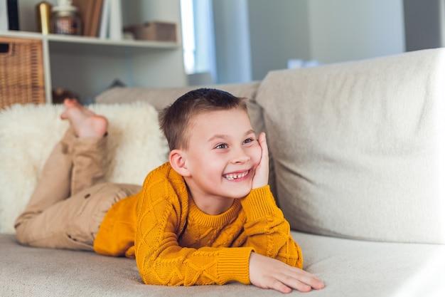 6 세 행복 소년 소파에 쉬고있다.