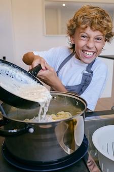 鍋のスパゲッティにカルボナーラソースを加える幸せな少年