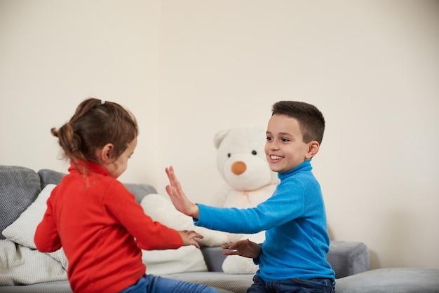 행복 한 소년과 소녀는 함께 연주하는 동안 그들의 손을 박수.