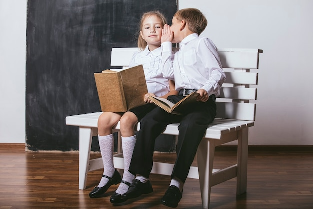 벤치에 초등학교 수업에서 행복 한 소년과 소녀는 슬레이트의 배경에 책을 읽고