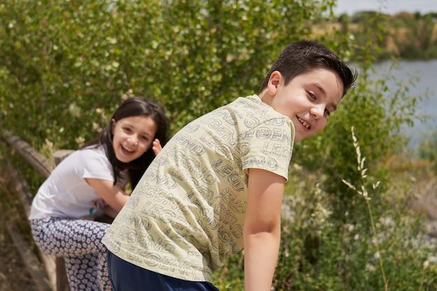 공원에서 나무 울타리에 올라 웃는 행복한 소년과 소녀