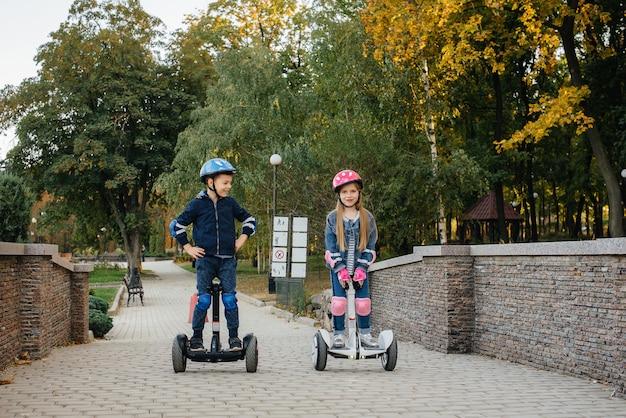 幸せな男の子と女の子は、日没時の暖かい秋の日に公園でセグウェイに乗ります。休んで、歩いてください。