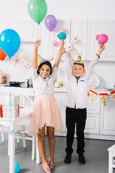 幸せな男の子と女の子が手にカラフルな風船を持って台所に立っています。