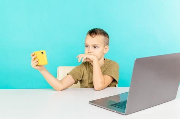 Счастливый мальчик на дистанционном обучении разговаривает по телефону с кем-то и использует компьютер для учебы.