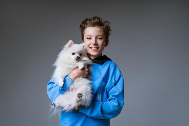 파란색 옷을 입고 행복 한 소년 금발, 회색 벽에 흰 개를 들고 눈이 하얀 이빨로 웃고