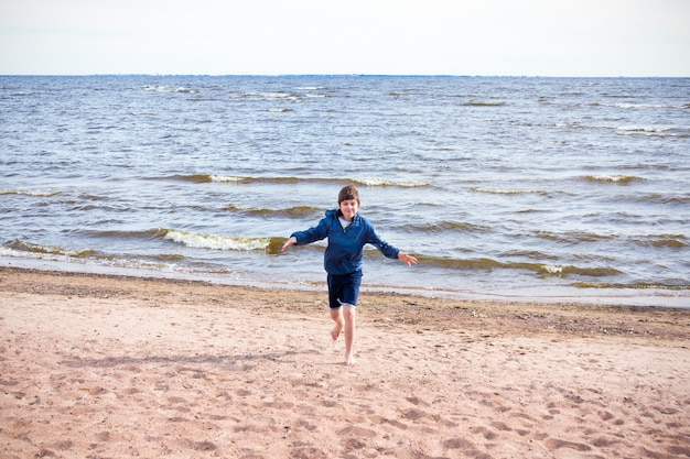 Happy boy in blue jacket and shorts barefooted running on sand on the beach, sunny day.