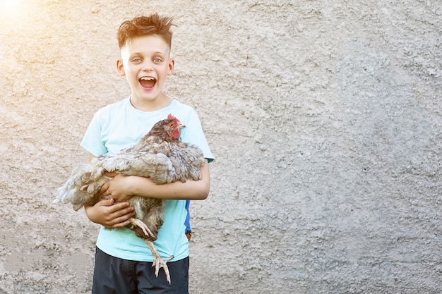 A happy boy in blue t-shirt holding chicken and laughing on blurred