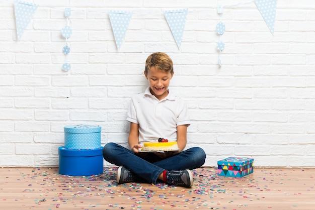 Happy boy celebrating his birthday with a cake