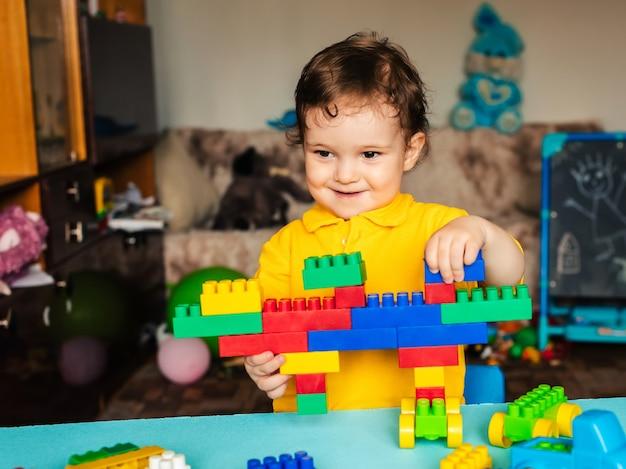 色のブロックで自宅で遊んで幸せな男の子の子供