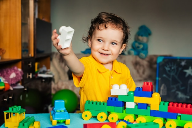 Happy boy child playing at home with colored blocks
