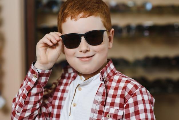 Счастливый мальчик, выбирая солнцезащитные очки в оптическом магазине.