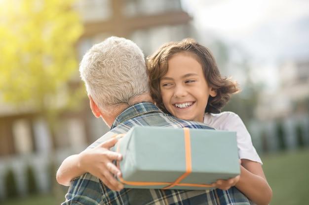 Счастливый мальчик. милый мальчик держит подарок и обнимает отца