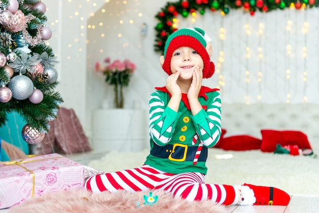 Счастливый мальчик, одетый как гном, сидит на полу в своей гостиной во время рождества