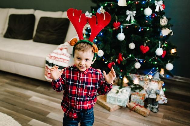 クリスマスツリーの近くの鹿の角の頭に幸せな少年のドレス。夜のクリスマスの家族。家族での休暇を楽しんでいます。メリークリスマス、そしてハッピーニューイヤー。