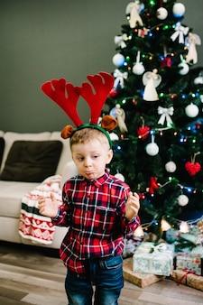 Счастливый мальчик одевается на голову из рогов оленя возле елки.