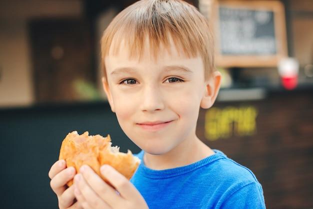 屋外のカフェでパンを食べて幸せな少年。