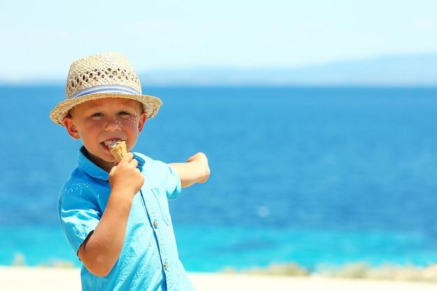海の近くでアイスクリームを食べる幸せな少年 Premium写真