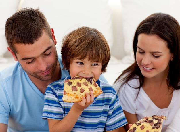 Счастливый мальчик ест пиццу с их родителями