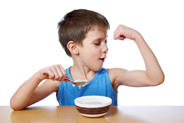 Happy boy eating porridge at table isolated