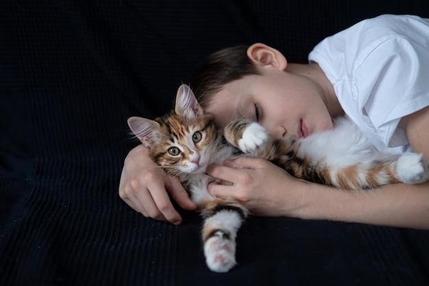 Счастливый мальчик обнимает молодого котенка курильского бобтейла