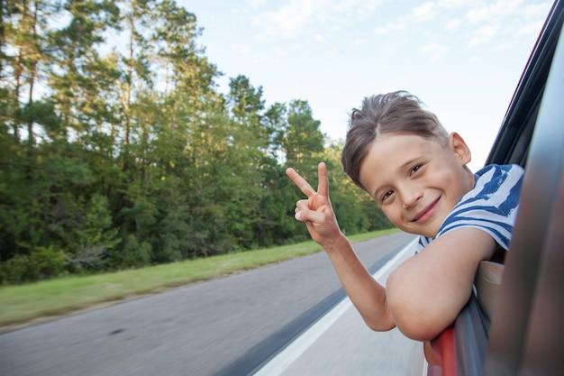 Happy boy enjoying a trip by the car. smiling boy peeking out the car's window. happy boy looking out window of a moving car.