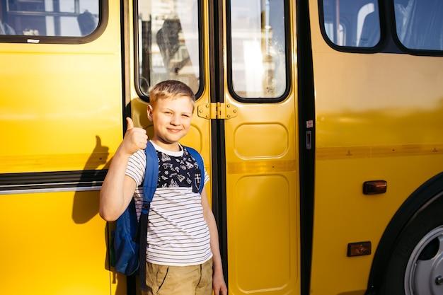 Happy boy in front of school bus