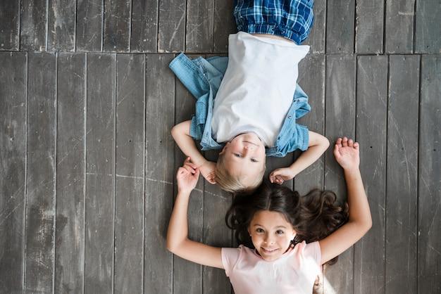 Happy boy and girl lying on hardwood floor