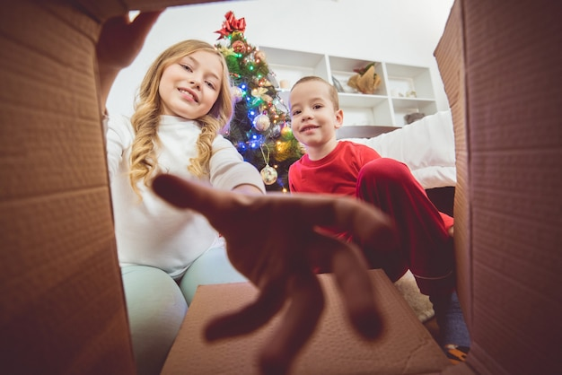 The happy boy and a girl open the box on the christmas tree background