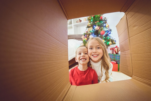 The happy boy and a girl open the box near the christmas tree