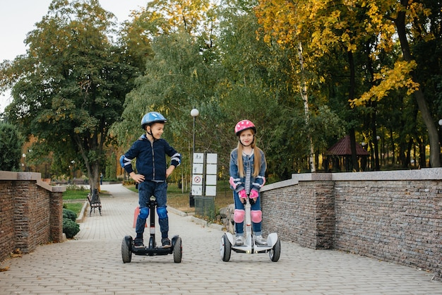 Happy boy and girl ride segways in the park on a warm autumn day during sunset. rest, and walk.
