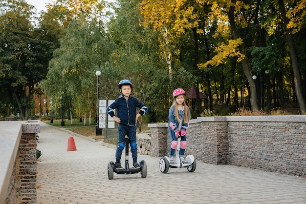 Happy boy and girl ride segways in the park on a warm autumn day during sunset