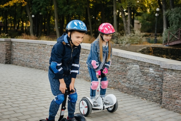 Happy boy and girl ride segways in the park on a warm autumn day during sunset.