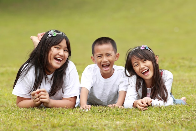 Happy boy and girls lying on a green grass