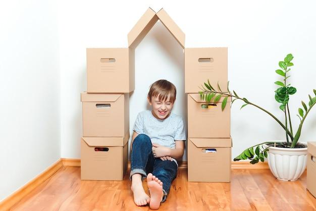 新しい家に移動する日を楽しんでいる幸せな少年。子供と一緒に若い家族を収容する。家族は新しいアパートに引っ越します。