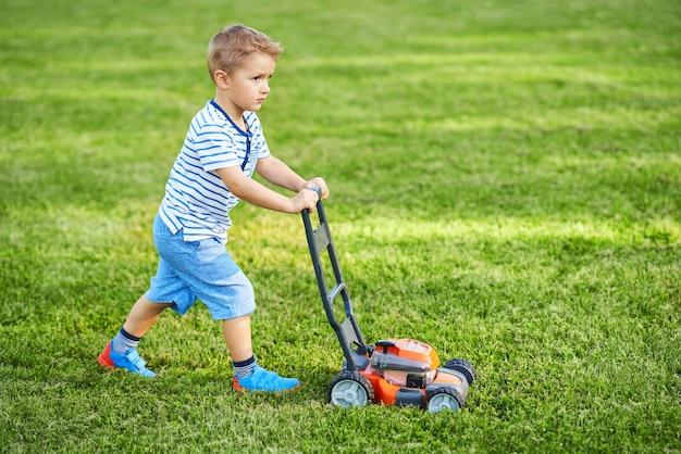 Счастливый мальчик с удовольствием косит лужайку
