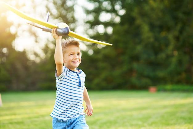 Счастливый мальчик весело играет с большим самолетом на открытом воздухе