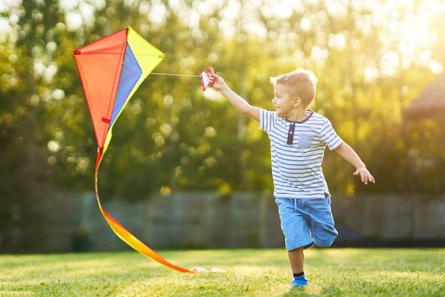 Счастливый мальчик весело играет с воздушным змеем