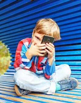 Happy boy having fun with a smartphone