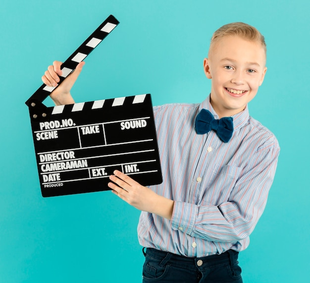 Happy boy holding clapperboard front view