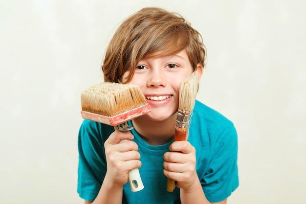 페인트 붓을 들고 행복 한 소년입니다. 아들은 부모가 벽을 페인트하도록 도와줍니다. 가족을위한 새 집. 주택 개조.
