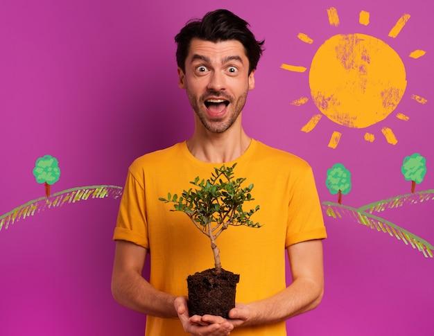 幸せな少年は、明るい色の上に植えられる準備ができている小さな木を持っています。植林、生態学および保全の概念