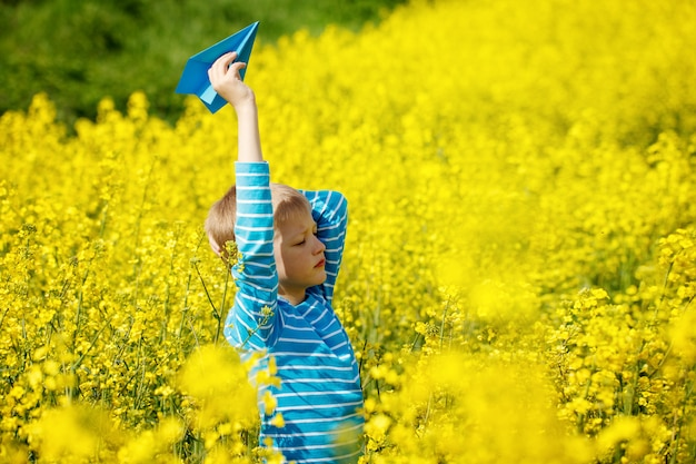 Happy boy holds in hand blue paper airplane on bright sunny day in the yellow field fowers