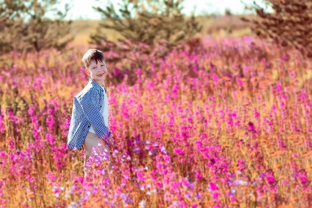 Счастливый мальчик в поле с яркими цветами. поле с розовыми цветами. мальчик собирает цветы в поле