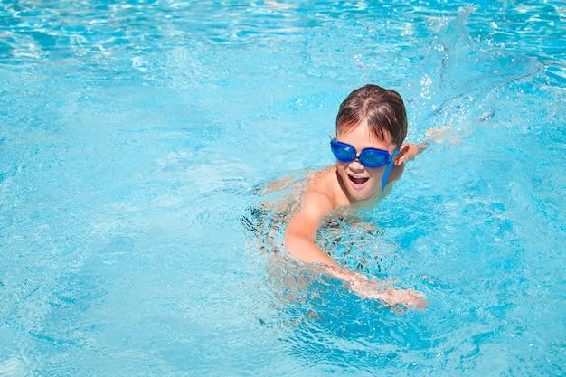 スイミングプールで幸せな少年。スイミングプールで楽しんでいるかわいい男の子。屋外。子供のためのスポーツ活動。