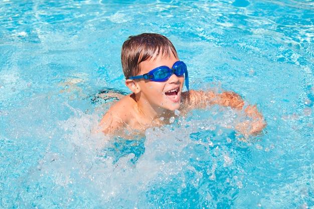 Счастливый мальчик в бассейне. милый маленький мальчик малыша весело в бассейне.