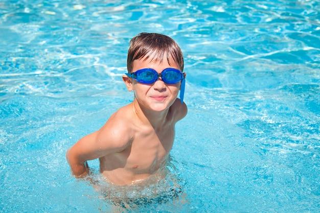 Счастливый мальчик в бассейне. спортивные занятия для детей.