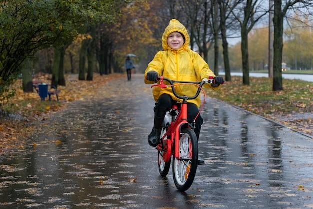 Счастливый мальчик в желтом плаще едет на велосипеде по мокрой аллее под дождем. осенний день