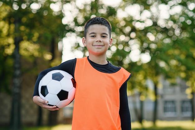 Счастливый мальчик в футбольной форме с мячом после тренировки на стадионе