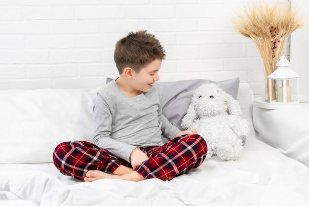 Счастливый мальчик в пижаме сидит на кровати со своей белой пушистой игрушкой