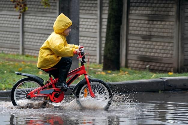 Счастливый мальчик в плаще весело едет на велосипеде по лужам. ребенок на велосипеде под дождем.